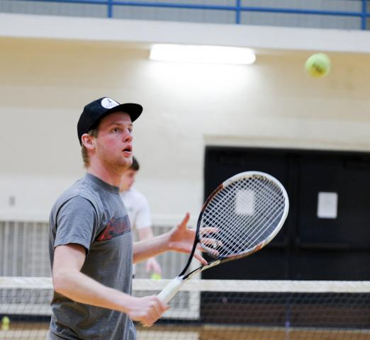 Luke Pascoe throws the tennis ball in preparation for a hard hit across the court. Pascoe, a senior from Arkansas, is part of the men's tennis team, consisting of 11 members.